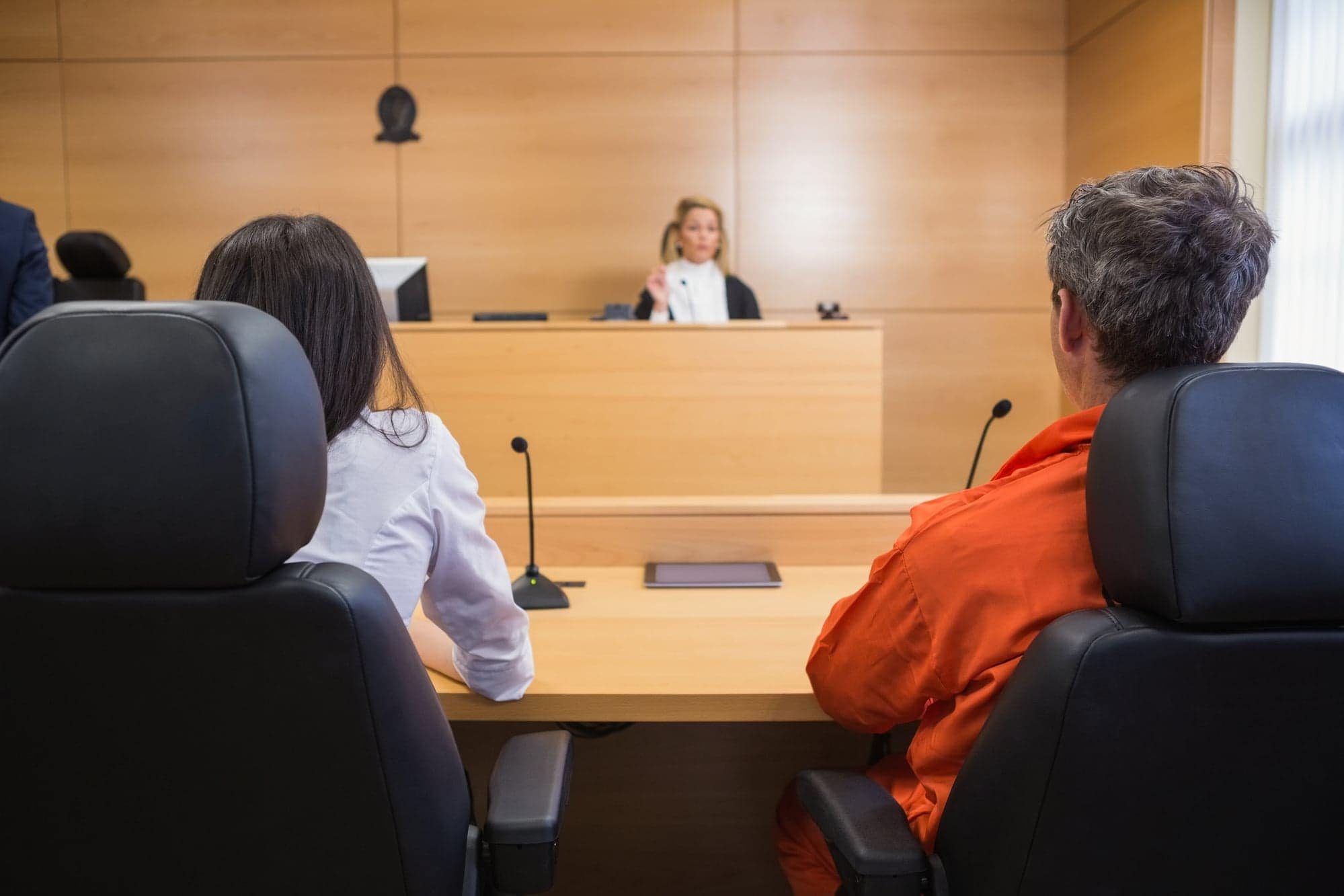 Lawyer and client listening to judge in the court room